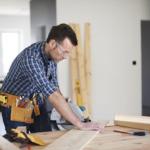 man sawing wood plank